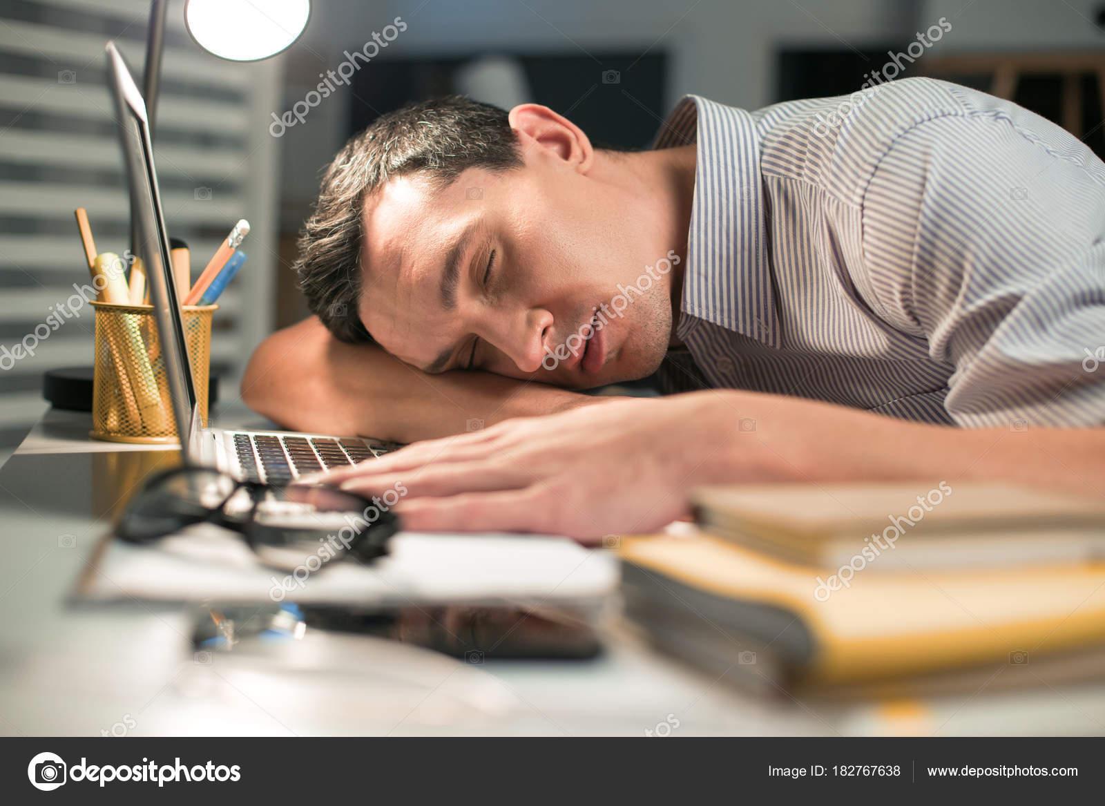 Geschickte männliche Mitarbeiter beim Einschlafen während der Arbeit ...