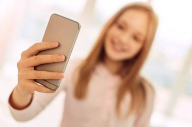 Fair-haired girl holding phone and taking selfie