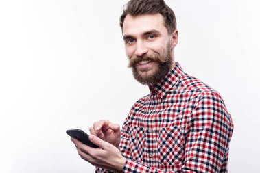 Smiling bearded man posing while typing message on phone