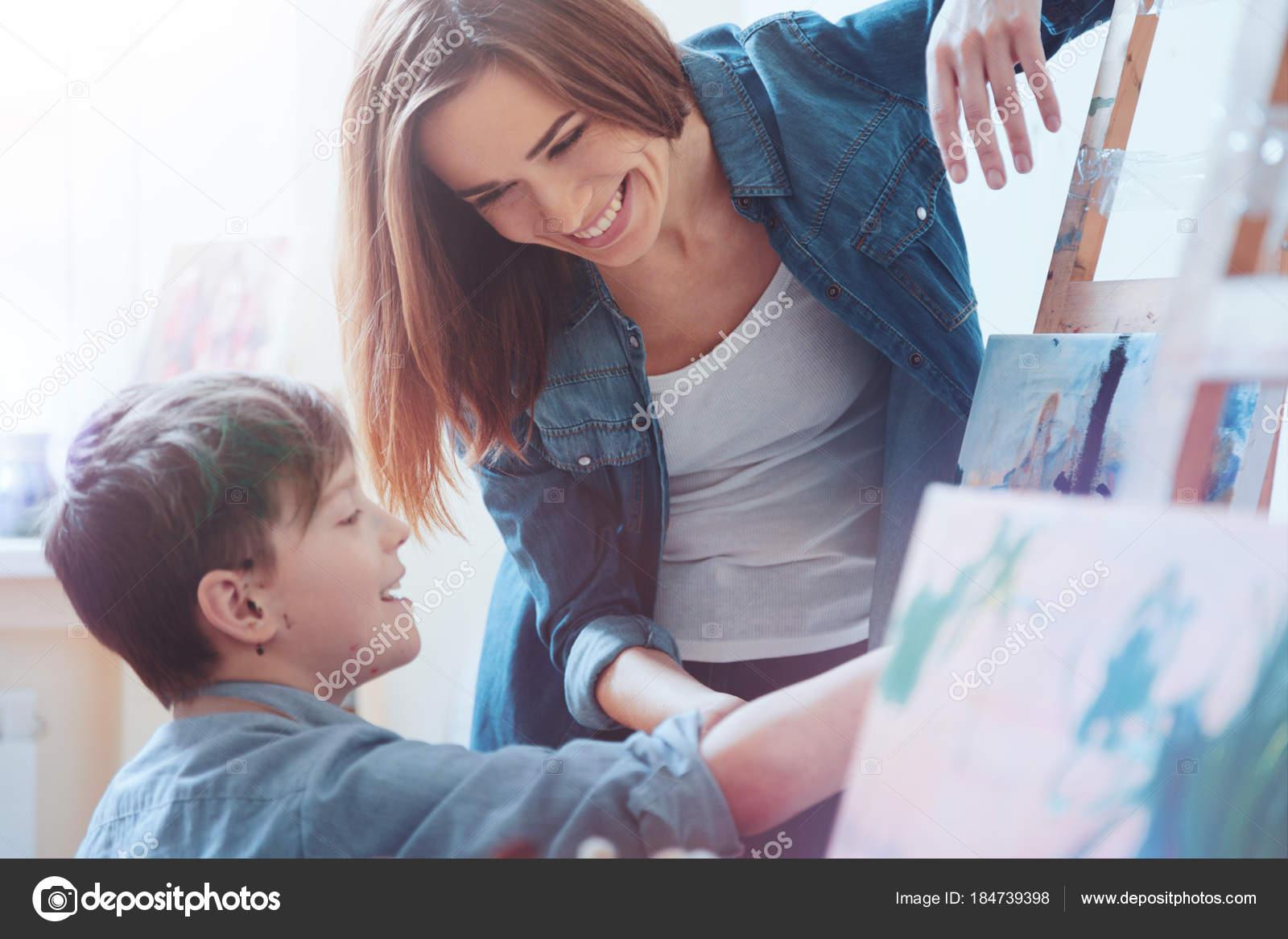 5185b0d3d Atitude positiva para trabalhar. Pintor feminino positivo, trabalhando em  um estúdio de pintura amplamente sorrindo enquanto olha para o menino de  cabelos ...