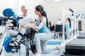 Šťastného starce v invalidního vozíku a jeho usmívající se trenér