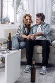 Mosolyogva, miközben ül férjével, nyugodt, vidám nő