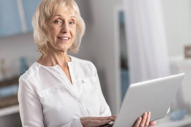 Musing mature woman studying online