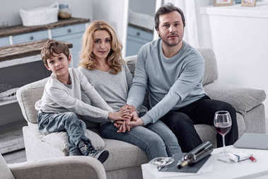 Calm family sitting on the sofa and holding their hands