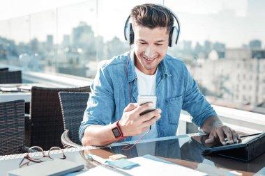 Joyful young gentleman turning on playlist while sitting on terrace