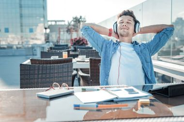 Relaxed freelancer listening to music after working hard