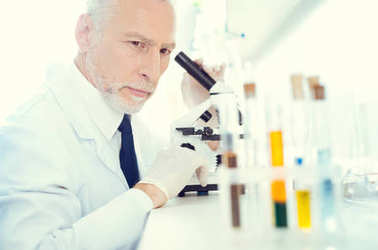 Serious lab worker with microscope looking at test tubes