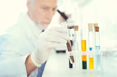 Close up of researcher taking test tube during research