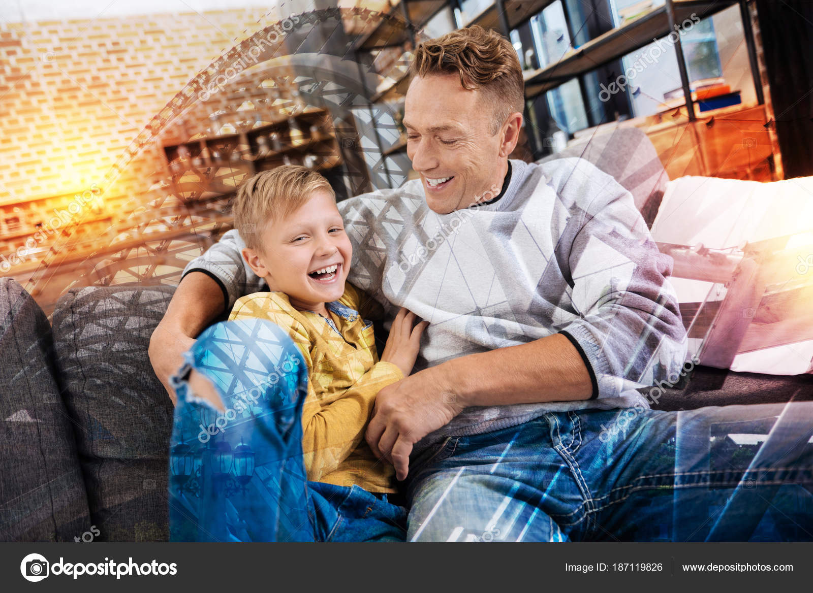 Emotional caring attentive father looking at his little happy son and  hugging him while sitting on a comfortable sofa together and laughing —  Photo by ...