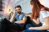 Fotografie Eifersüchtige Frau zeigt eine Telefon zu ihrem Freund während mit Verdacht