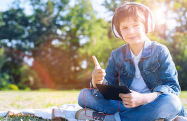 Cheerful kid thumbing up while listening to music