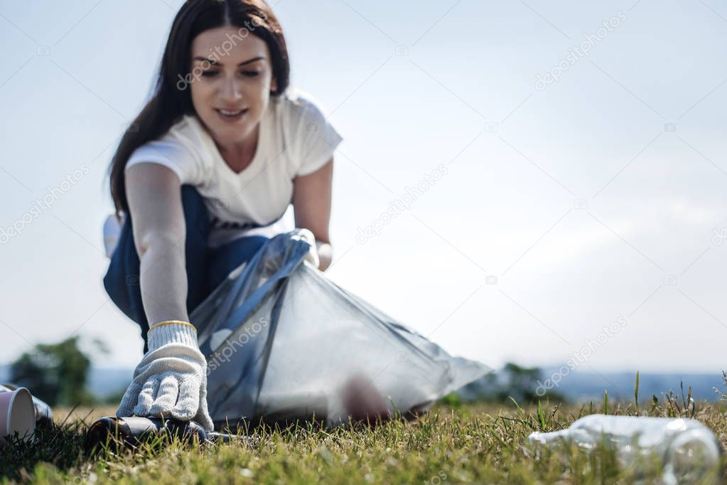 Pleasant young woman collecting bottles