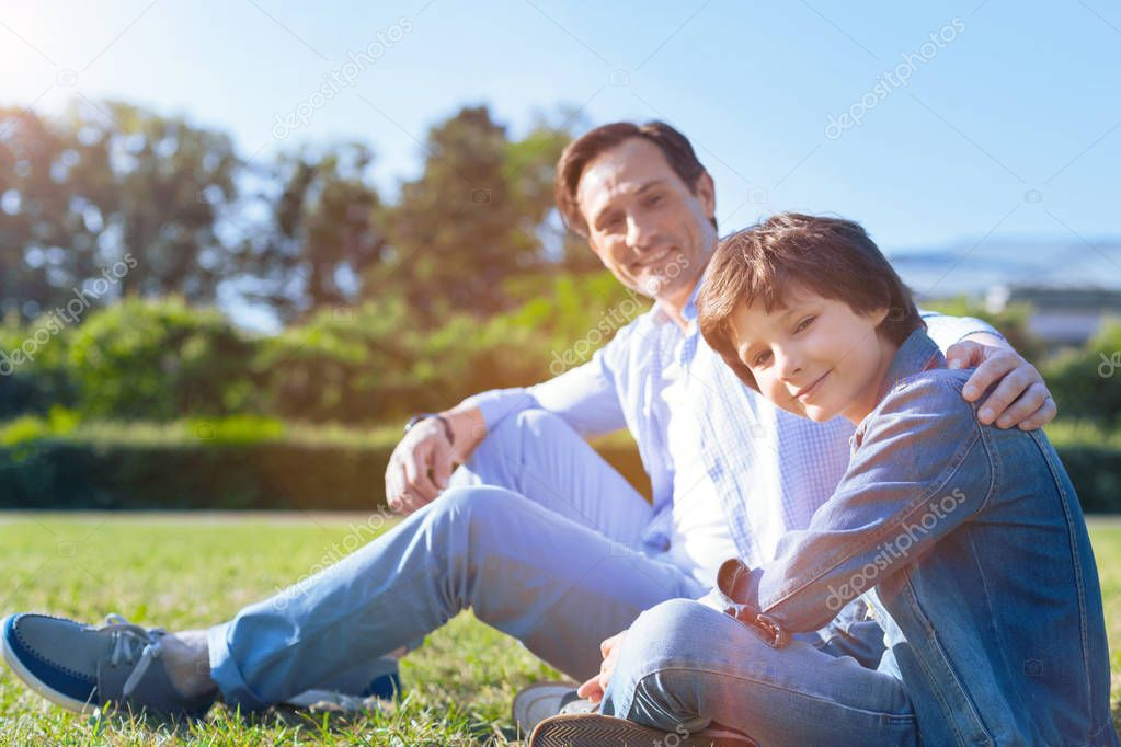 Harmonious father and son relaxing on grass together