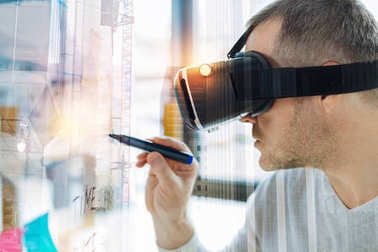 Serious man in virtual reality glasses looking calm and holding a marker
