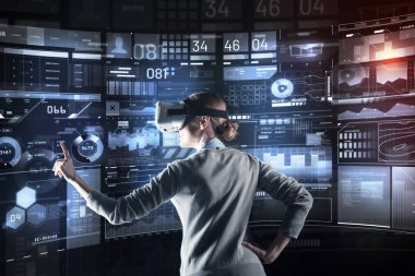 Excellent. Calm attentive cheerful programmer looking careful and pointing to the screen while working in convenient virtual reality glasses stock vector
