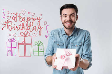 Emotional young man holding a present while being at the birthday party