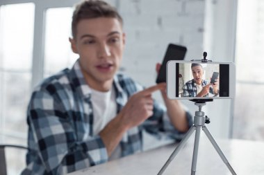 Great phone. Attractive delighted famous well-built teenager holding his phone and talking about it while making a video stock vector