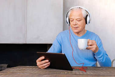 Delighted aged man watching a video