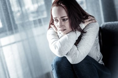 Stressful unhappy woman hugging herself and looking down.