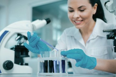 Careful lab assistant mixing reagents