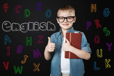 Smart kid putting his thumb up and feeling happy to learn English