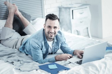Cheerful handsome man doing an online course