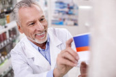 Joyful male pharmacist putting drug on shelf