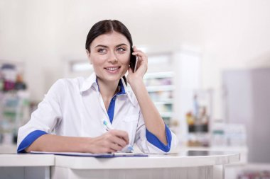 Medicine supply. Inspired female pharmacist calling while taking notes stock vector
