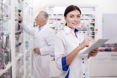 Charming female pharmacist developing electronic system