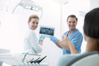 Delighted dentists showing teeth on the screen