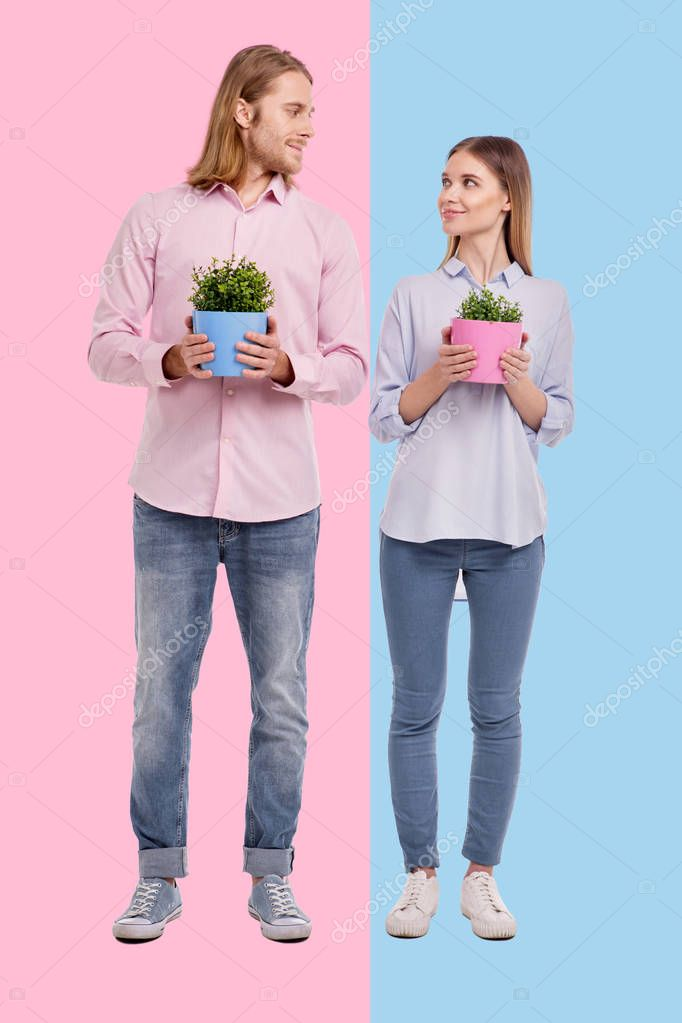 Happy couple posing with flower pots and exchanging loving looks