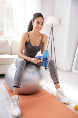 Cheerful woman drinking water during workout session