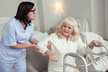 Beautiful nurse giving elder woman leg up