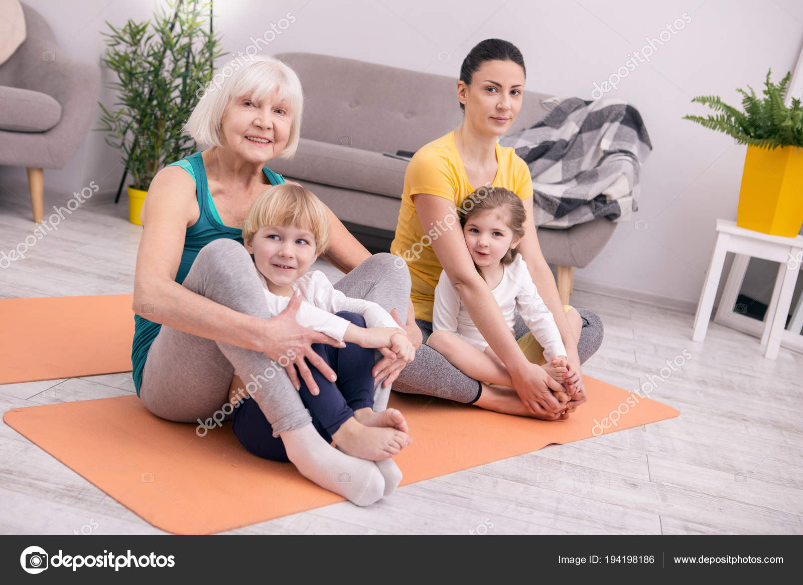 Smiling women and kids doing yoga — Stock Photo © yacobchuk1