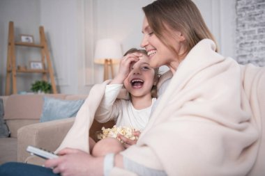 Happy mother and daughter eating popcorn