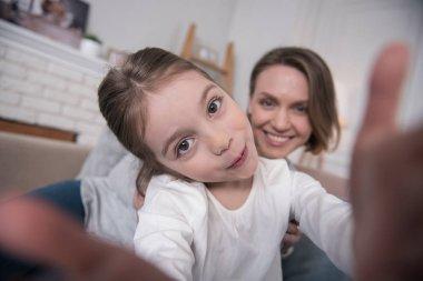 Smiling mummy and daughter taking selfies