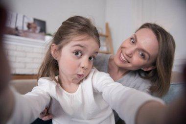 Alert mummy and daughter taking selfies