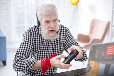 White-haired elderly man playing video game excitingly