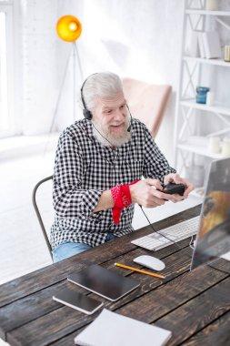 Upbeat senior man having fun while playing video game