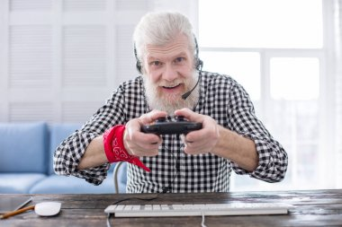 Cheerful elderly man using game controller while playing