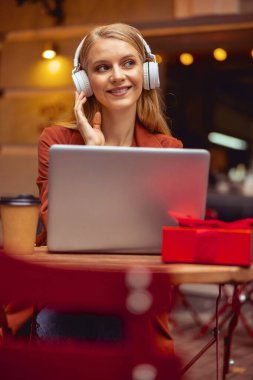 Delighted girl listening to music at the table