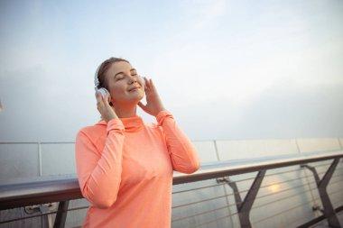Smiling lady listening to music through wireless headphones