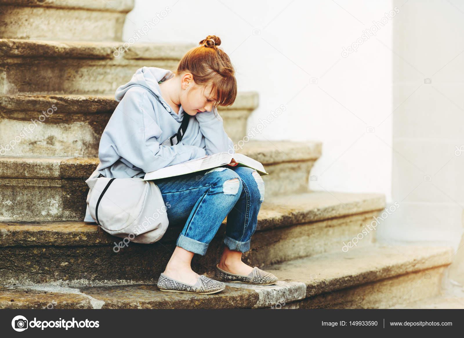 f7ace1151 Kid niña leyendo libro afuera, sentado en las escaleras, con mochila ...