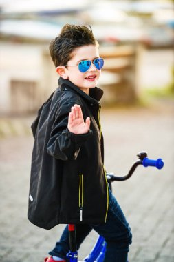 Little kid boy riding a bike, looking back over his shoulder, wearing black jacket and sunglasses