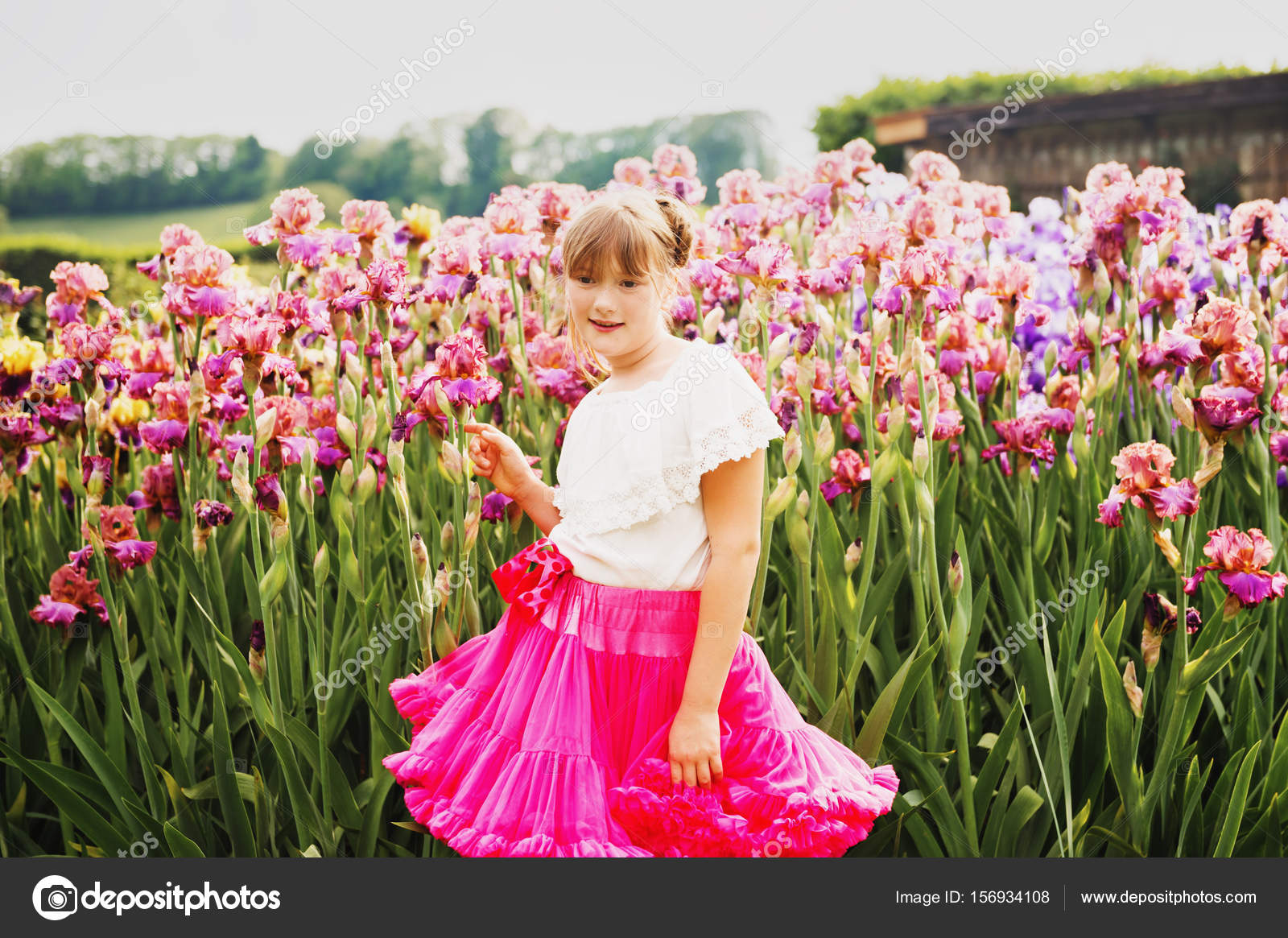 Cute little girl playing in iris flower garden on a nice summer day cute little girl playing in iris flower garden on a nice summer day wearing white shirt and bright pink tutu skirt photo by annanahabed izmirmasajfo Gallery