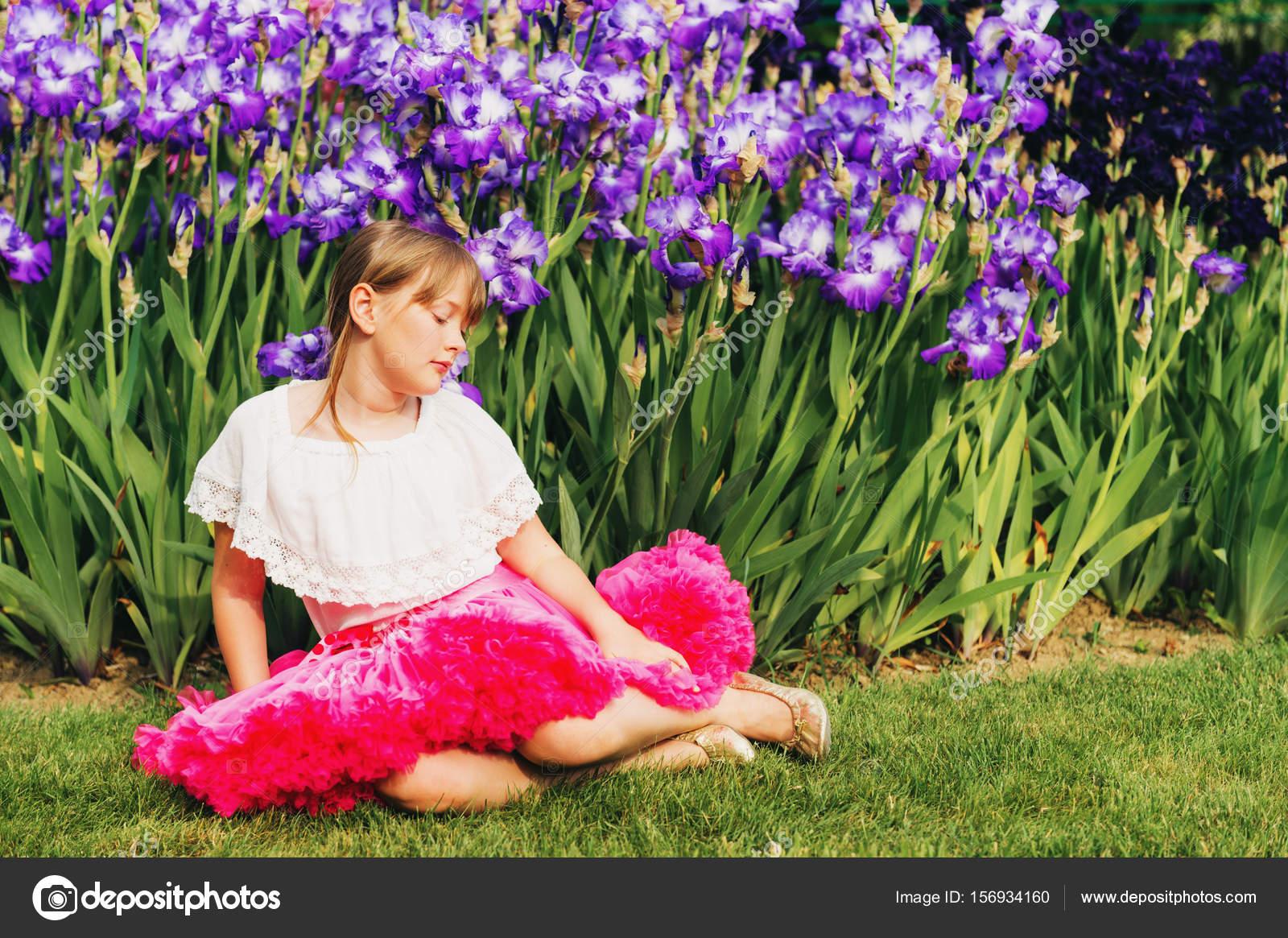 Cute little girl playing in iris flower garden on a nice summer day cute little girl playing in iris flower garden on a nice summer day wearing white izmirmasajfo Gallery