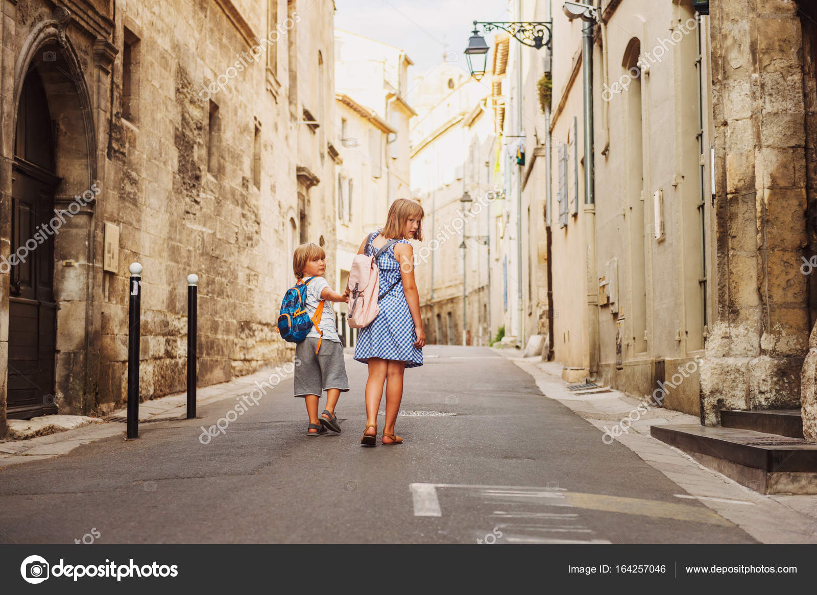 Group Of Two Kids Walking On The Streets Of Old European Town