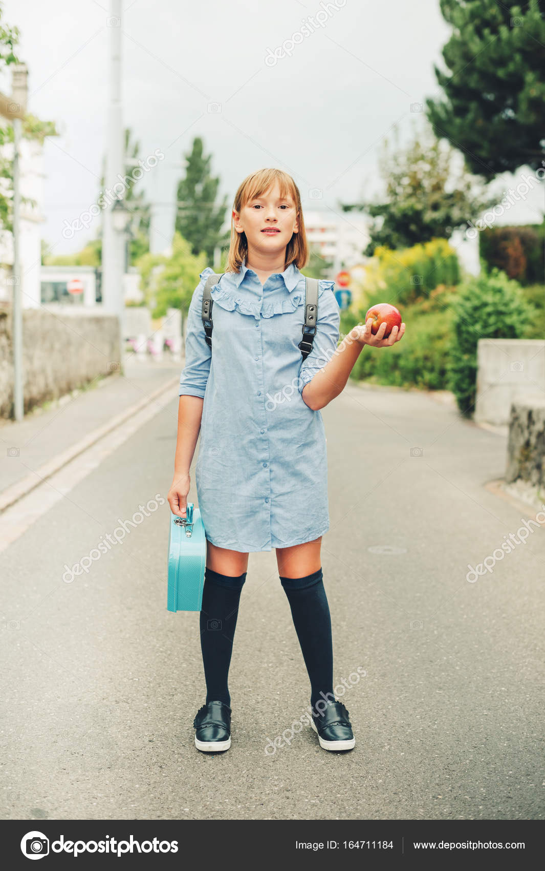 Outdoor portrait of funny little schoolgirl, wearing formal dress ...