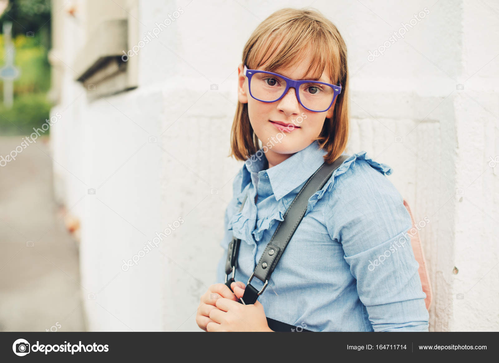 d333eab64e3e Outdoor portrait of a cute little 9-10 year old girl wearing blue uniform  dress