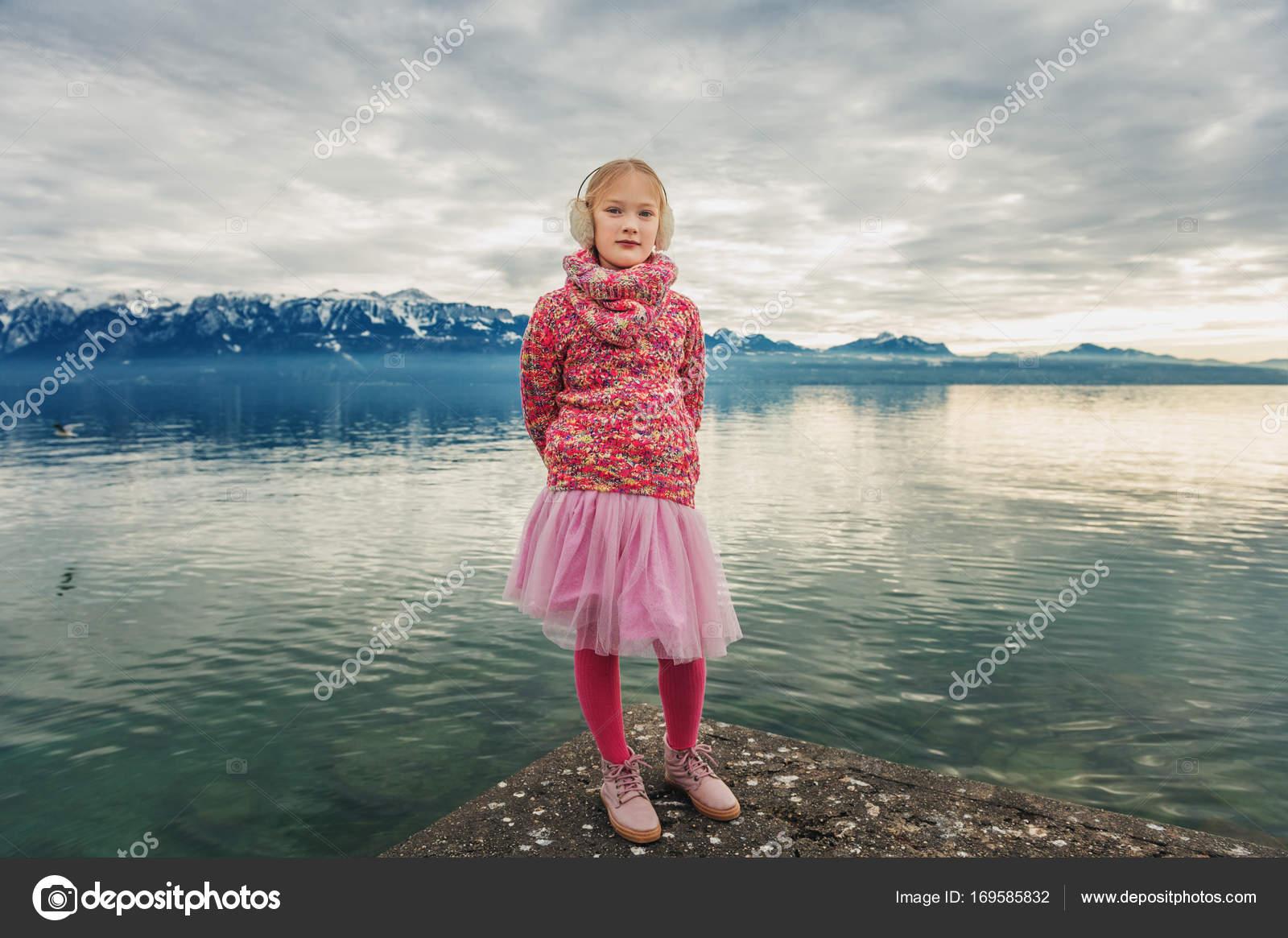aa6ac444b1e9 Entzückende kleine Mädchen ruhen am Genfer See an einem kalten Wintertag  tragen warmen rosa Pullover, Tutu Rock, Strumpfhosen und Schuhe, ...